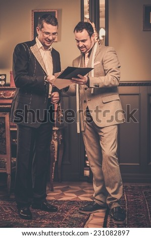 Tailor and client choosing cloth and buttons for custom made suit  - stock photo