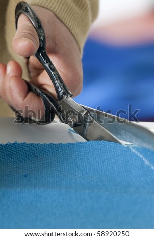 tailor cuts a piece of cloth with scissors - stock photo