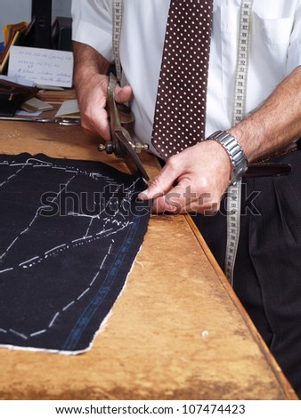 Tailor hands working in a coat. - stock photo