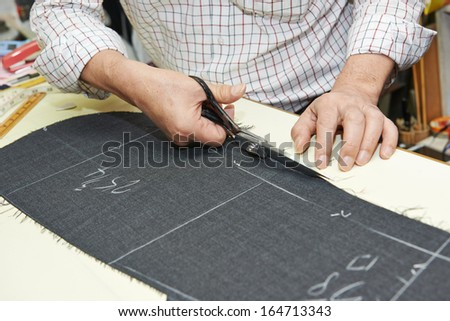Tailor hands working with scissor and suit textile cloth - stock photo