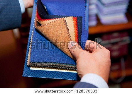 tailor. Man searching through fabrics for a suit - stock photo