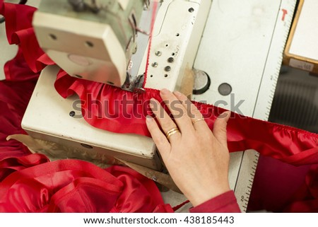 Tailor's hand on sewing machine fastening red satin ribbon on cloth. - stock photo