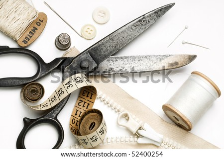 tailor's tools - scissors, spool of thread, pins, zipper, etc. - on white - stock photo