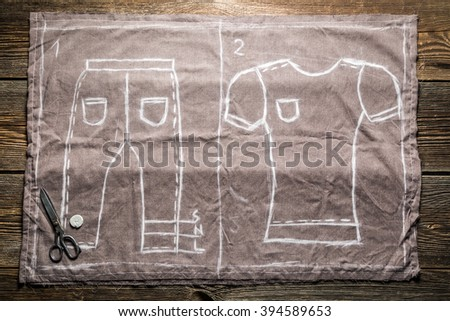 Tailor sketch shirts and trousers on the material - stock photo