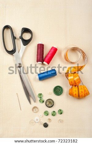 Tailor tools for craft. Set from measuring tape, buttons, bobbins of thread, needle and scissors on linen canvas - stock photo