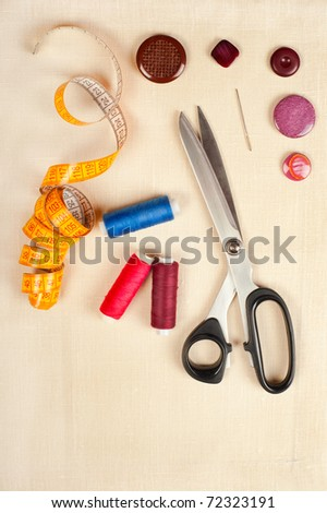 Tailor tools for craft. Set from measuring tape, buttons, bobbins of thread, needle and scissors on linen - stock photo