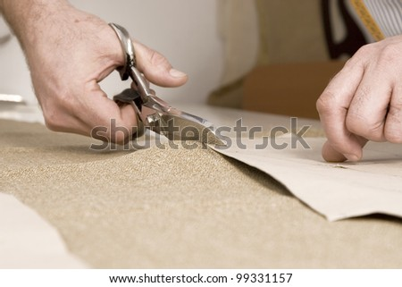 Tailor working at studio cutting fabric, detail of hand with scissors - stock photo