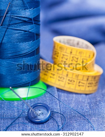 tailoring still life - thread bobbin with needle, button, measure tape on blue silk dress - stock photo