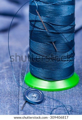 tailoring still life - thread bobbin with needle, button on blue silk cloth - stock photo