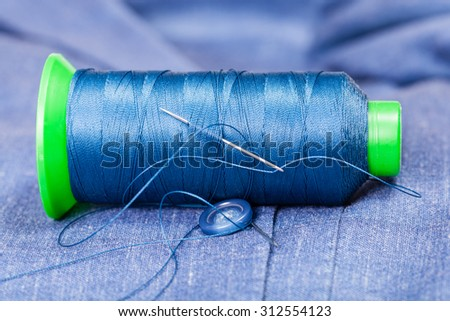 tailoring still life - thread bobbin with needle, button on blue silk jacket - stock photo