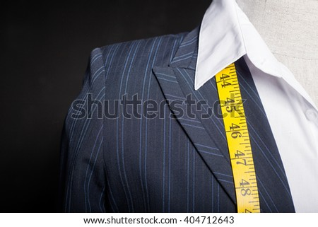 Tailors mannequin with measure tape - stock photo