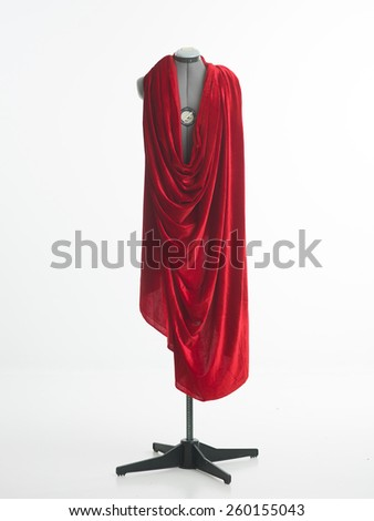 tailors mannequin with red fabric on top, with white background - stock photo