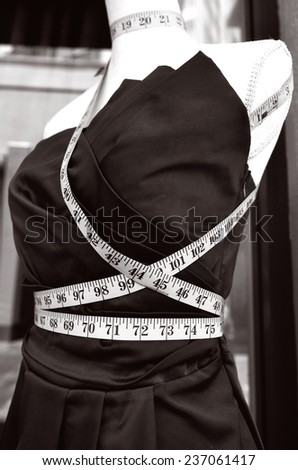 Tailors purple textile dress dummy with measure tape. - stock photo