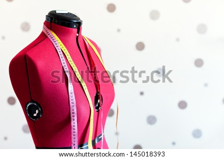 tailors red textile dummy with two measure tapes - stock photo