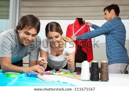 Tailors working together with colleague measuring red fabric on mannequin in background - stock photo