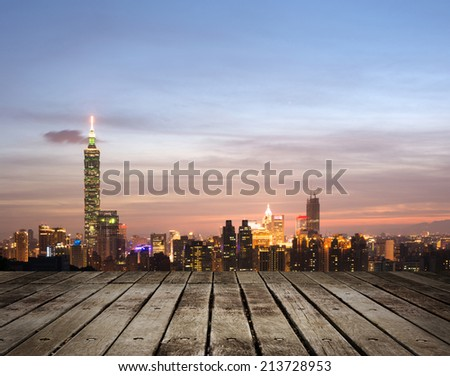 Taipei city night with famous landmark, 101 skyscraper, under blue and dramatic colorful sky in Taiwan, Asia. Focus on wooden floor. - stock photo