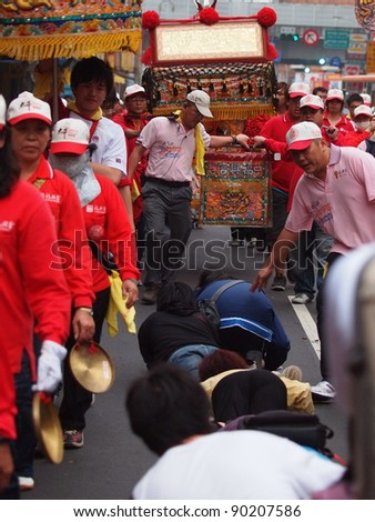 TAIPEI, TAIWAN - APRIL 16: People are creeping through a Matsu's sedan chair to pray for peace in a temple fair in Taipei, Taiwan on April 16, 2011. Matsu is Chinese sea god. - stock photo