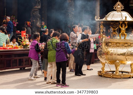 TAIPEI, TAIWAN - APRIL 23: people pray in Longshan temple in Taipei, Taiwan on April 23th 2015. Longshan Temple worships a mixture of Buddhist and Taoist deities. - stock photo