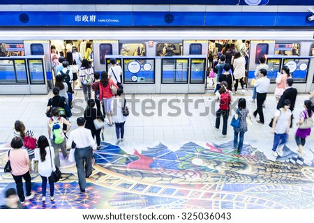 TAIPEI,TAIWAN - JANUARY 19: Passengers waiting and ride the MRT, on January 19,2014 in Taipei. The (Metropolitan Rapid Transit) MRT serves 240,000 people daily with 109 stations and 121 km of track. - stock photo