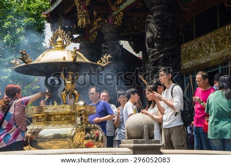 TAIPEI, TAIWAN - May 3,2015 : a group of people pray and offering in Longshan temple in Taipei, Taiwan on May 3rd, 2015. Longshan Temple worships a mixture of Buddhist and Taoist deities. - stock photo