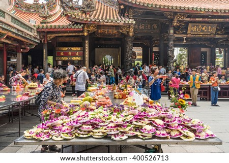 Taipei, Taiwan - May 03,2015 : Taiwanese  offering food, flowers and incense sticks for the Gods in Longshan Temple on May 3rd, 2015. Longshan Temple worships a mixture of Buddhist and Taoist deities. - stock photo