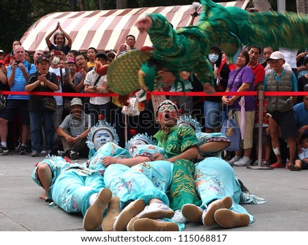 TAIPEI, TAIWAN-OCT 4: Traditional entertainment  is performed in the Northern Taiwan Mazhu Festival in Taipei, Taiwan on October 4, 2012. A player somersaults over the players lain on the ground. - stock photo