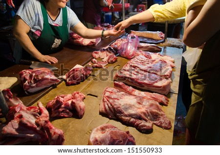 TAIPEI, TAIWAN - October 7 : A buyer buy the pork with the butcher in the dark and traditional marketplace on October 7, 2012 in Taipei, Taiwan, Asia. - stock photo