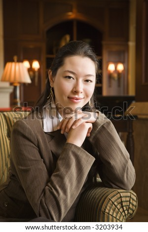 Taiwanese mid adult buisinesswoman looking at viewer with chin resting on hands. - stock photo