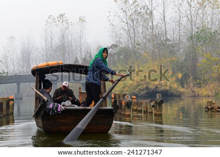 TAIZHOU, CHINA - NOVEMBER 22, 2014: An unidentified woman propels the boat that takes tourists on a tour of Qinhu National Wetland Park outside of TaiZhou China.  They often sing traditional songs. - stock photo