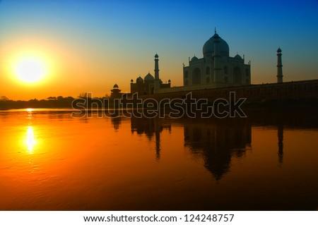 Taj Mahal sunrise reflection in River with blue sky - stock photo