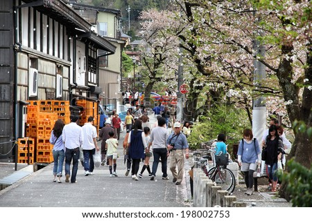 TAKAYAMA, JAPAN - APRIL 29, 2012: Visitors enjoy cherry blossom in Takayama, Japan. Takayama is among top 25 tourism destinations in Japan according to Japan-Guide.com. - stock photo