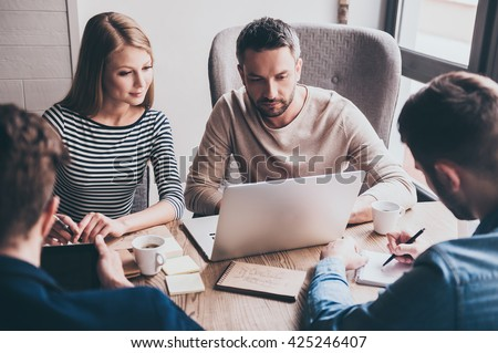 Take a look at this chart! Young handsome man using laptop while sitting at the office table on business meeting with his coworkers - stock photo