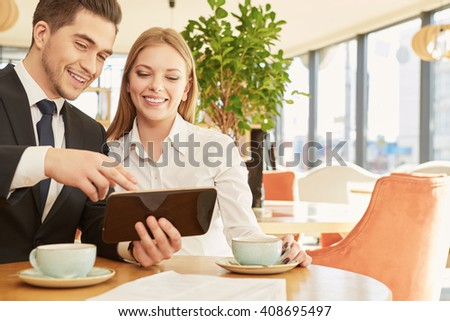 Take a look. Young handsome businessman smiling cheerfully showing something in his tablet to his beautiful smiling colleague - stock photo