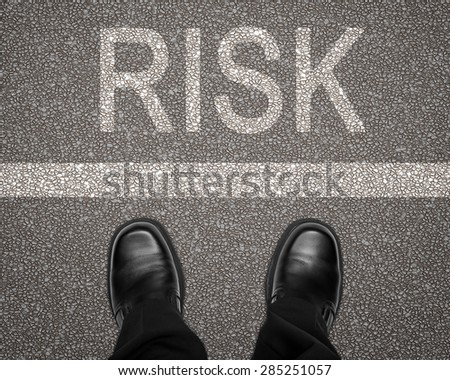 Take a risk concept with feet on road behind white line - stock photo