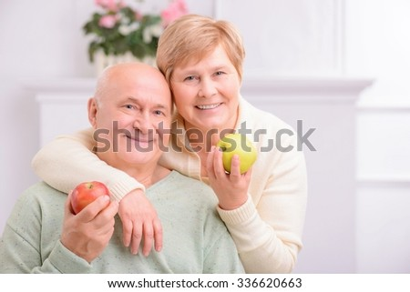 Take care of your health. Agreeable content adult couple holding apples and embracing while resting at home - stock photo