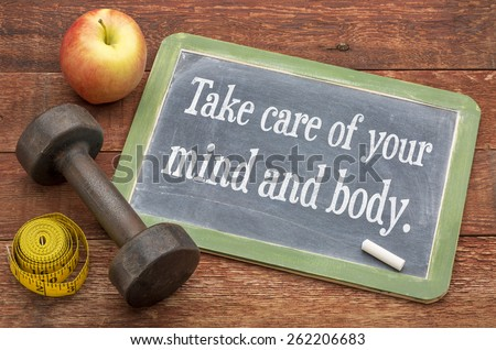 Take care of your mind and body -  slate blackboard sign against weathered red painted barn wood with a dumbbell, apple and tape measure - stock photo