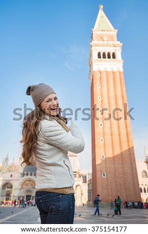 Take classical tourist enjoyment in Venice, Italy - wander over San Marco square, chase pigeons and take photos. Happy young woman pointing on bell tower of St Mark's Basilica - stock photo