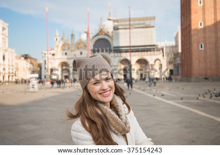 Take classical tourist enjoyment in Venice, Italy - wander over San Marco square, chase pigeons and take photos. Portrait of happy young woman standing on Piazza San Marco - stock photo