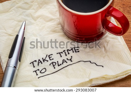 Take time to play advice on a napkin with a cup of coffee - work life balance concept - stock photo