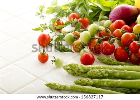 Taken on a white tile of summer vegetables - stock photo
