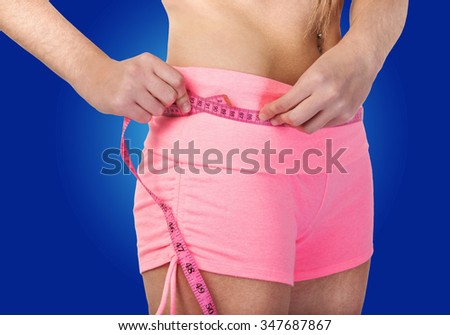 Taking a tape measure of exercise and diet results - stock photo