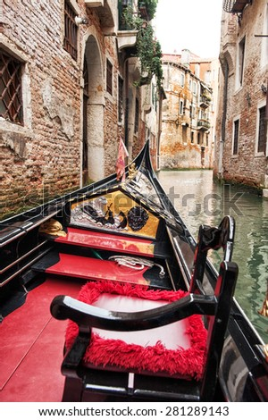Taking a tour in a Venetian gondola through the canals of the historic city of Venice, Italy, a UNESCO World Heritage Site and popular tourist destination - stock photo