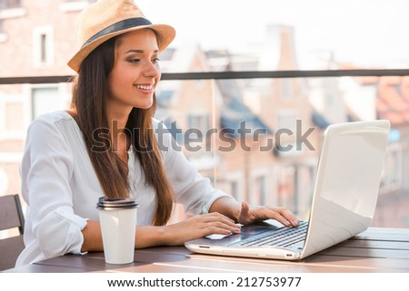 Taking advantages of free Wi-Fi. Beautiful young woman in funky hat working on laptop and smiling while sitting outdoors - stock photo