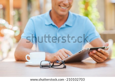 Taking advantages of free Wi-Fi. Close-up of cheerful mature man writing something in his note pad and smiling while sitting at the table outdoors with house in the background  - stock photo