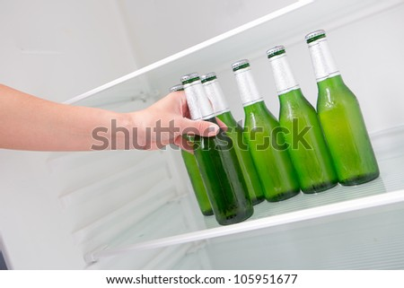 Taking beer from a fridge - stock photo