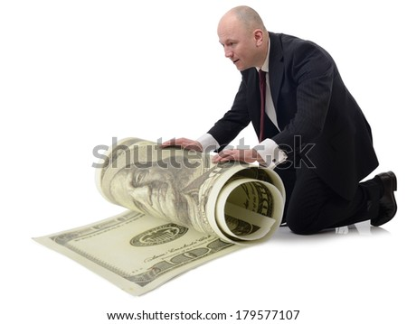 taking care of money a man rolling up a large 100 dollar bill isolated on a white background. - stock photo