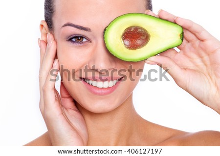 Taking care of your skin the natural way. Beautiful young shirtless woman holding piece of avocado in front of her eye and touching her face while standing against white background - stock photo