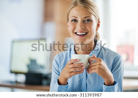 Taking coffee break. Cheerful young businesswoman in formalwear holding cup of coffee and looking at camera while sitting at her working place - stock photo