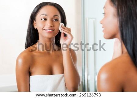 Taking good care of her face. Beautiful young African woman cleaning her face with sponge and smiling while standing against a mirror in bathroom  - stock photo