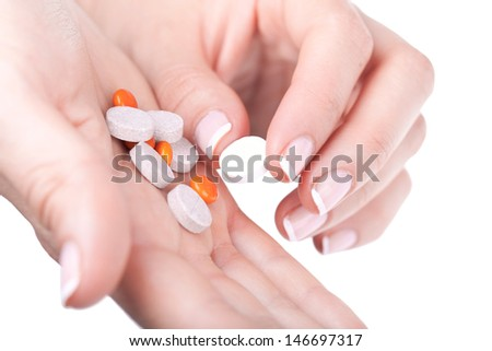 Taking one pill from pile, closeup on white  - stock photo